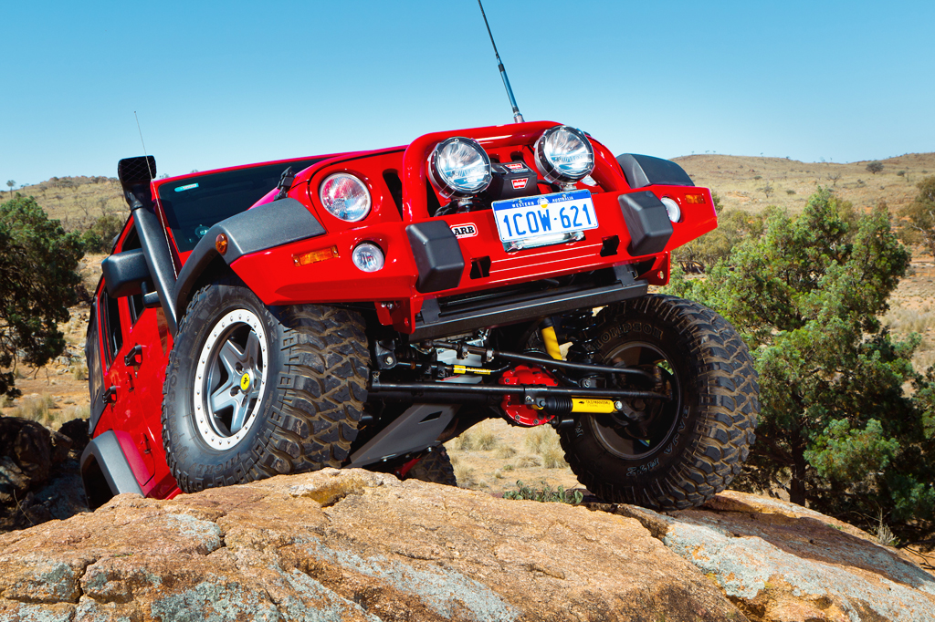 Bright red Jeep JK with lift kit, snorkel and accessories